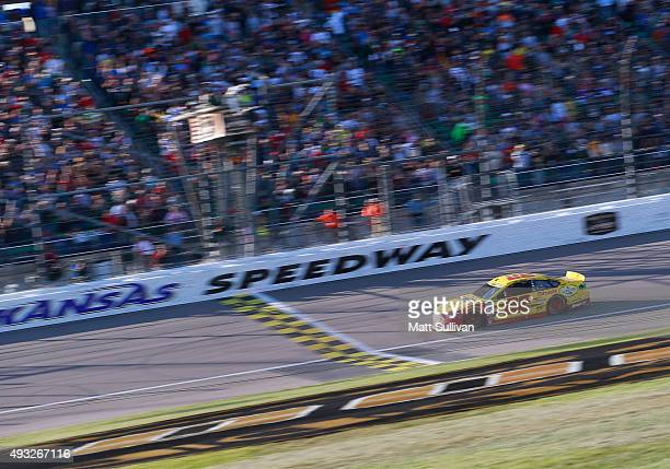 Joey Logano driver of the Shell Pennzoil Ford takes the checkered flag to win the NASCAR Sprint Cup Series Hollywood Casino 400 at Kansas Speedway on...