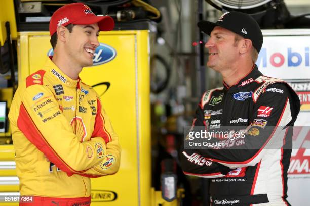 Joey Logano driver of the Shell Pennzoil Ford talks with Clint Bowyer driver of the Haas Automation Ford in the garage area during practice for the...