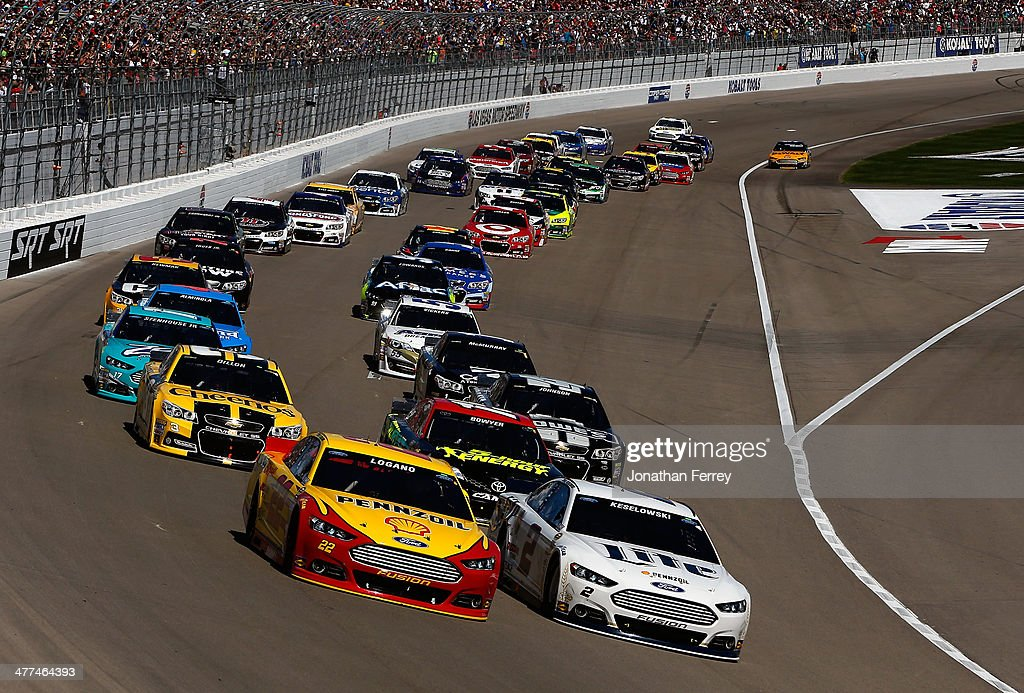 <a gi-track='captionPersonalityLinkClicked' href=/galleries/search?phrase=Joey+Logano&family=editorial&specificpeople=4510426 ng-click='$event.stopPropagation()'>Joey Logano</a>, driver of the #22 Shell-Pennzoil Ford, and <a gi-track='captionPersonalityLinkClicked' href=/galleries/search?phrase=Brad+Keselowski&family=editorial&specificpeople=890258 ng-click='$event.stopPropagation()'>Brad Keselowski</a>, driver of the #2 Miller Lite Ford, lead the field to start the NASCAR Sprint Cup Series Kobalt 400 at Las Vegas Motor Speedway on March 9, 2014 in Las Vegas, Nevada.