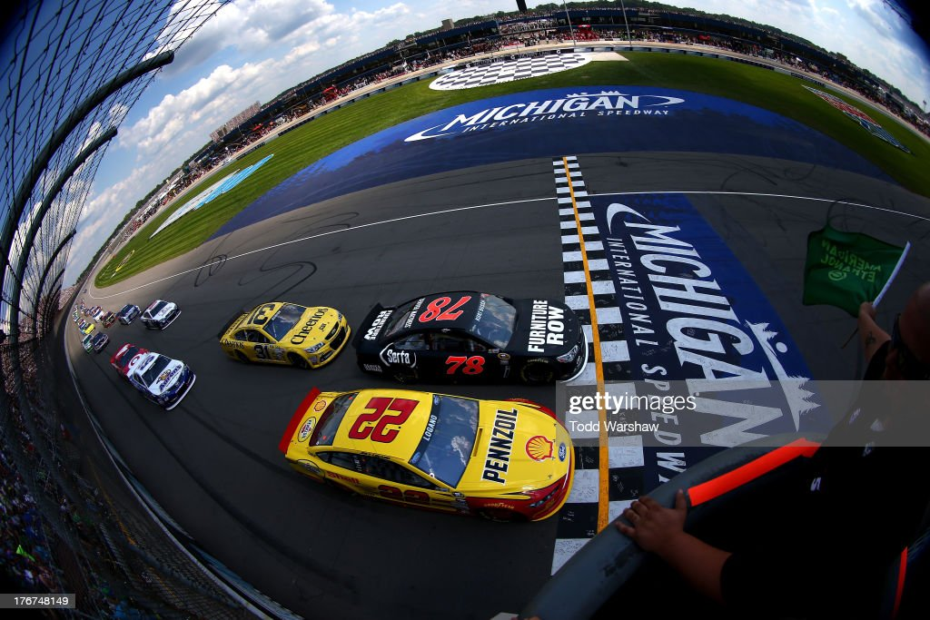 <a gi-track='captionPersonalityLinkClicked' href=/galleries/search?phrase=Joey+Logano&family=editorial&specificpeople=4510426 ng-click='$event.stopPropagation()'>Joey Logano</a>, driver of the #22 Shell-Pennzoil Ford, and <a gi-track='captionPersonalityLinkClicked' href=/galleries/search?phrase=Kurt+Busch&family=editorial&specificpeople=201728 ng-click='$event.stopPropagation()'>Kurt Busch</a>, driver of the #78 Furniture Row / Serta Chevrolet, lead the field to the start of the NASCAR Sprint Cup Series 44th Annual Pure Michigan 400 at Michigan International Speedway on August 18, 2013 in Brooklyn, Michigan.