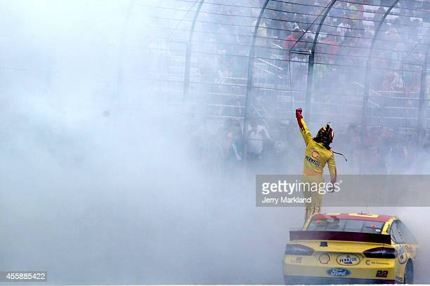 Joey Logano driver of the ShellPennzoil Ford celebrates after winning the NASCAR Sprint Cup Series Sylvania 300 at New Hampshire Motor Speedway on...