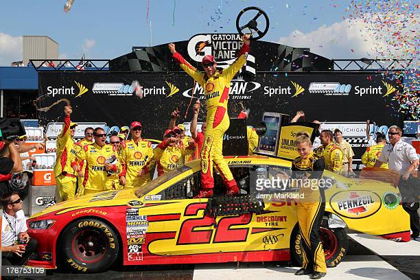 Joey Logano driver of the ShellPennzoil Ford celebrates in Victory Lane after winning the NASCAR Sprint Cup Series 44th Annual Pure Michigan 400 at...