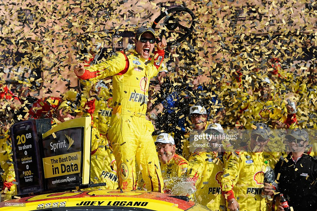 Joey Logano driver of the ShellPennzoil Ford celebrates in Victory Lane after winning the NASCAR Sprint Cup Series Hollywood Casino 400 at Kansas...