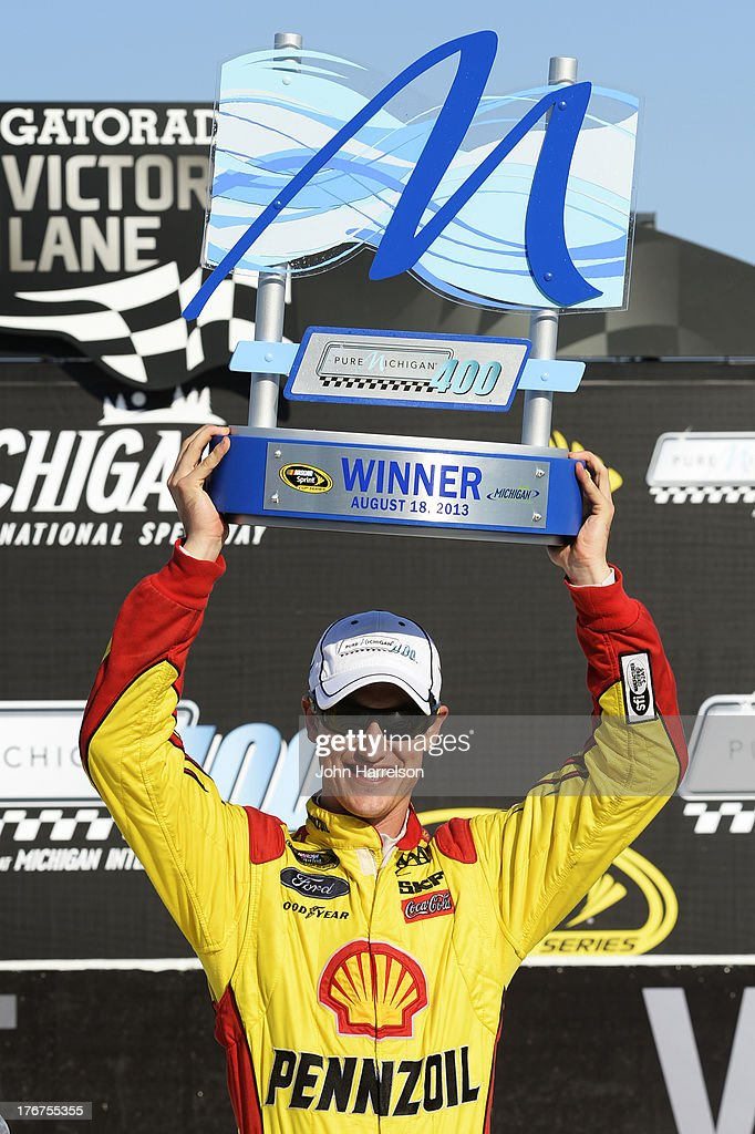 <a gi-track='captionPersonalityLinkClicked' href=/galleries/search?phrase=Joey+Logano&family=editorial&specificpeople=4510426 ng-click='$event.stopPropagation()'>Joey Logano</a>, driver of the #22 Shell-Pennzoil Ford, celebrates the trophy in Victory Lane after winning the NASCAR Sprint Cup Series 44th Annual Pure Michigan 400 at Michigan International Speedway on August 18, 2013 in Brooklyn, Michigan.