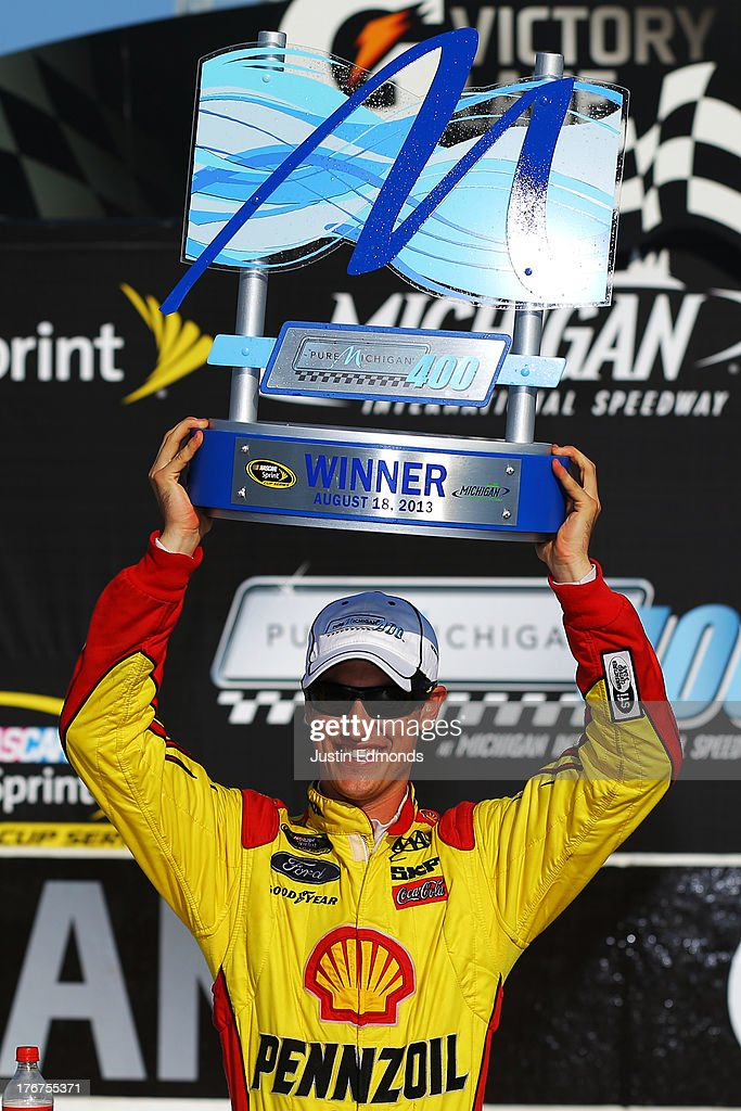 Joey Logano, driver of the #22 Shell-Pennzoil Ford, celebrates the trophy in Victory Lane after winning the NASCAR Sprint Cup Series 44th Annual Pure Michigan 400 at Michigan International Speedway on August 18, 2013 in Brooklyn, Michigan.