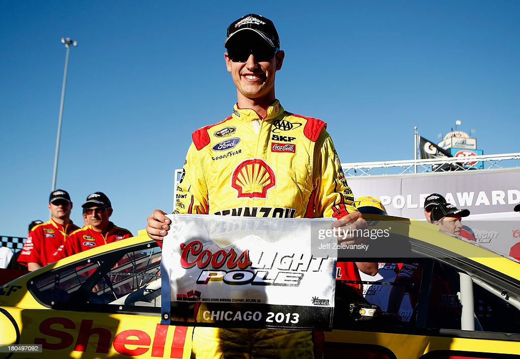 Joey Logano, driver of the #22 Shell-Pennzoil Ford, celebrates winning the pole award after qualifying first for the NASCAR Sprint Cup Series Geico 400 at Chicagoland Speedway on September 13, 2013 in Joliet, Illinois.