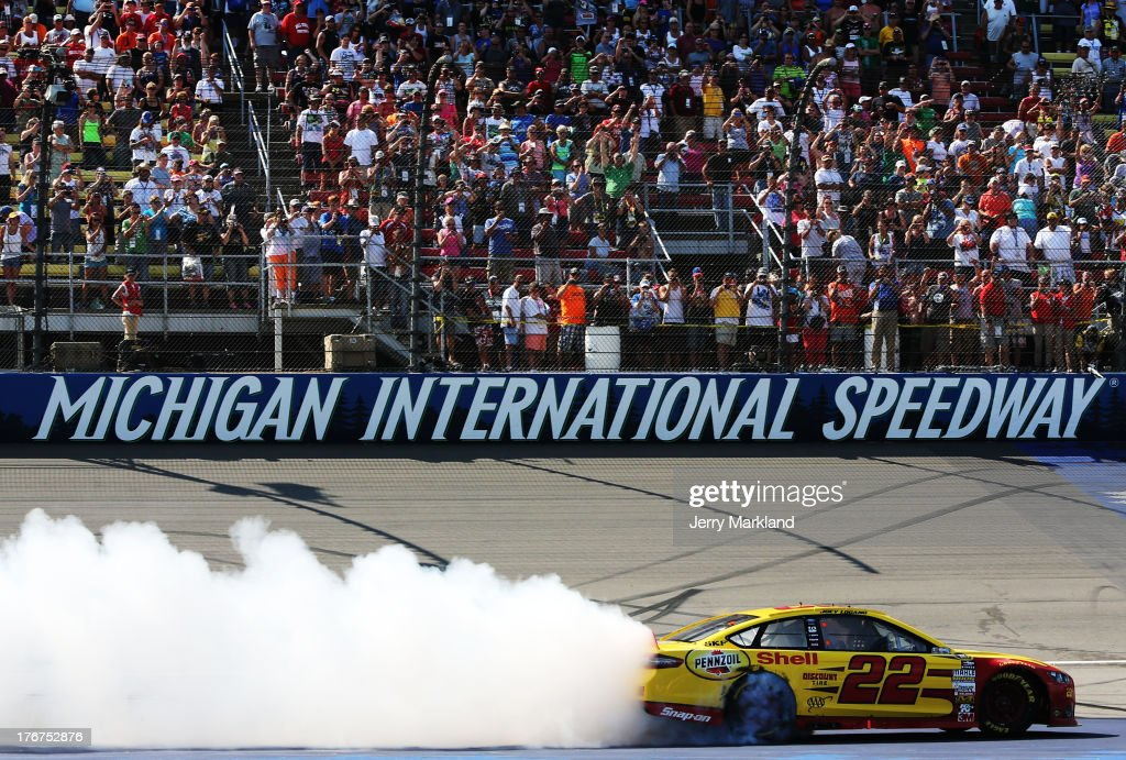 <a gi-track='captionPersonalityLinkClicked' href=/galleries/search?phrase=Joey+Logano&family=editorial&specificpeople=4510426 ng-click='$event.stopPropagation()'>Joey Logano</a>, driver of the #22 Shell-Pennzoil Ford, celebrates with a burnout after winning the NASCAR Sprint Cup Series 44th Annual Pure Michigan 400 at Michigan International Speedway on August 18, 2013 in Brooklyn, Michigan.