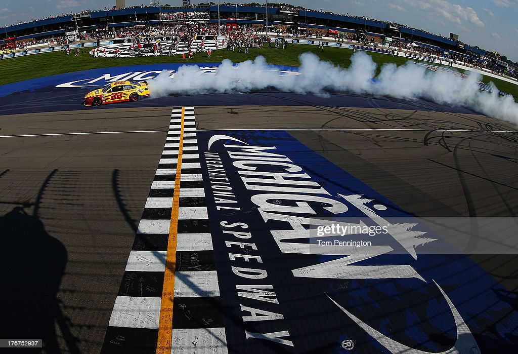 Joey Logano, driver of the #22 Shell-Pennzoil Ford, celebrates with a burnout after winning the NASCAR Sprint Cup Series 44th Annual Pure Michigan 400 at Michigan International Speedway on August 18, 2013 in Brooklyn, Michigan.