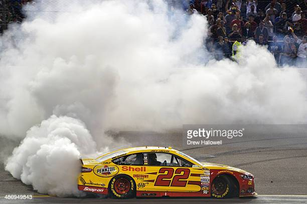 Joey Logano driver of the ShellPennzoil Ford celebrates with a burnout after winning the NASCAR Sprint Cup Series Toyota Owners 400 at Richmond...