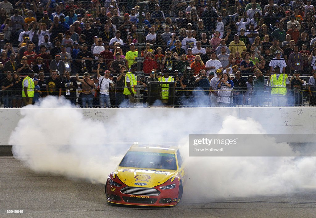 Joey Logano, driver of the #22 Shell-Pennzoil Ford, celebrates with a burnout after winning the NASCAR Sprint Cup Series Toyota Owners 400 at Richmond International Raceway on April 26, 2014 in Richmond, Virginia.