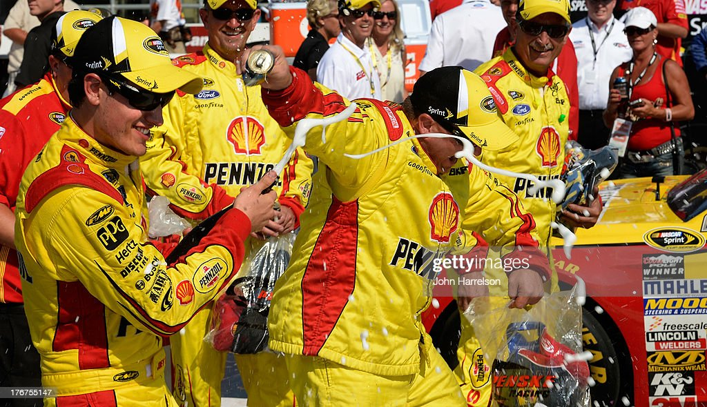 <a gi-track='captionPersonalityLinkClicked' href=/galleries/search?phrase=Joey+Logano&family=editorial&specificpeople=4510426 ng-click='$event.stopPropagation()'>Joey Logano</a>, driver of the #22 Shell-Pennzoil Ford, celebrates with champagne in Victory Lane after winning the NASCAR Sprint Cup Series 44th Annual Pure Michigan 400 at Michigan International Speedway on August 18, 2013 in Brooklyn, Michigan.