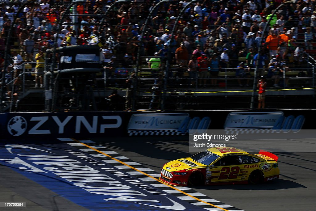 Joey Logano, driver of the #22 Shell-Pennzoil Ford, crosses the finishline to win the NASCAR Sprint Cup Series 44th Annual Pure Michigan 400 at Michigan International Speedway on August 18, 2013 in Brooklyn, Michigan.