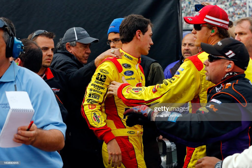 Joey Logano driver of the ShellPennzoil Ford gets held back by his crew member after an altercation with Denny Hamlin driver of the FedEx Freight...