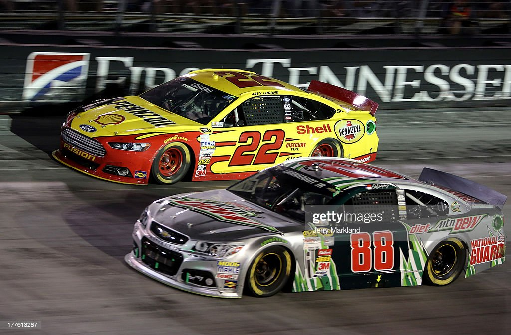 Joey Logano, driver of the #22 Shell-Pennzoil Ford, races Dale Earnhardt Jr., driver of the #88 Diet Mountain Dew Chevrolet, during the NASCAR Sprint Cup Series 53rd Annual IRWIN Tools Night Race at Bristol Motor Speedway on August 24, 2013 in Bristol, Tennessee.