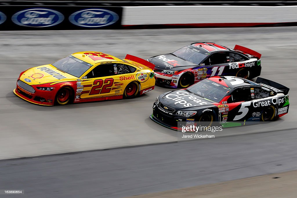 Joey Logano, driver of the #22 Shell-Pennzoil Ford, races Denny Hamlin, driver of the #11 FedEx Freight Toyota, and Kasey Kahne, driver of the #5 Great Clips Chevrolet, during the NASCAR Sprint Cup Series Food City 500 at Bristol Motor Speedway on March 17, 2013 in Bristol, Tennessee.
