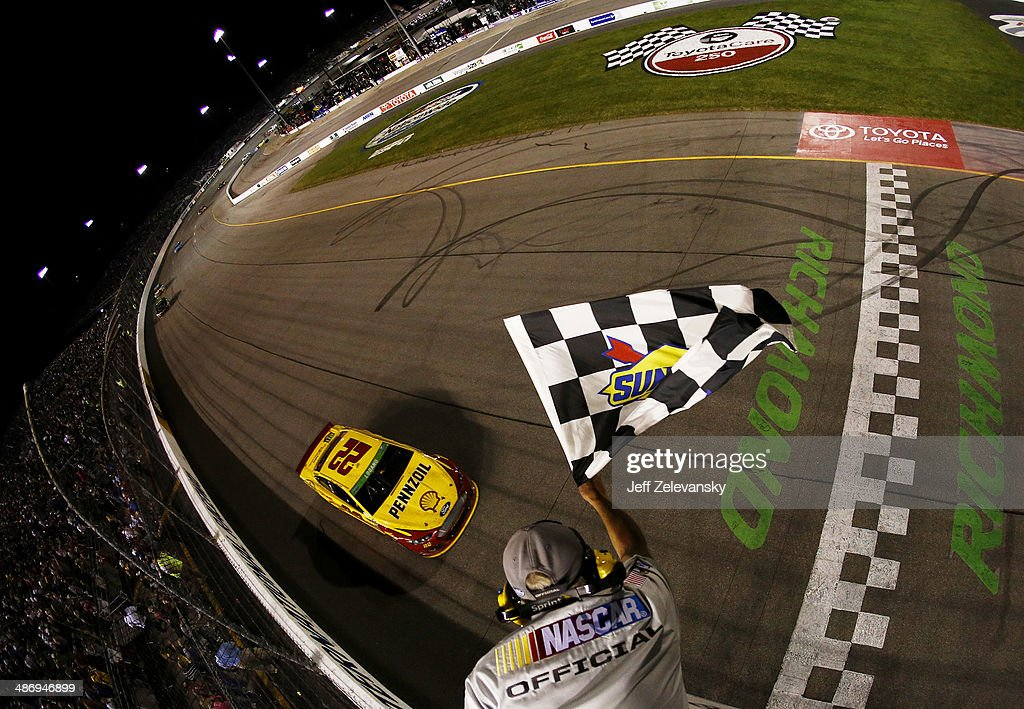 Joey Logano, driver of the #22 Shell-Pennzoil Ford, races to the checkered flag to win the NASCAR Sprint Cup Series Toyota Owners 400 at Richmond International Raceway on April 26, 2014 in Richmond, Virginia.