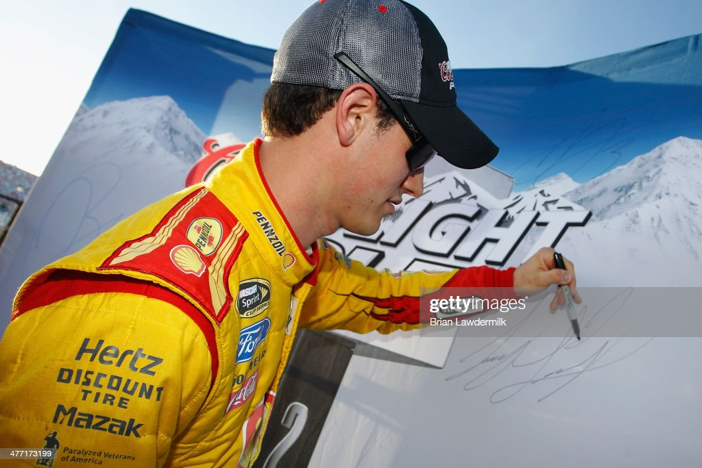 Joey Logano, driver of the #22 Shell-Pennzoil Ford, signs the backdrop after turning the fastest lap during qualifying for the NASCAR Sprint Cup Series Kobalt 400 at Las Vegas Motor Speedway on March 7, 2014 in Las Vegas, Nevada.