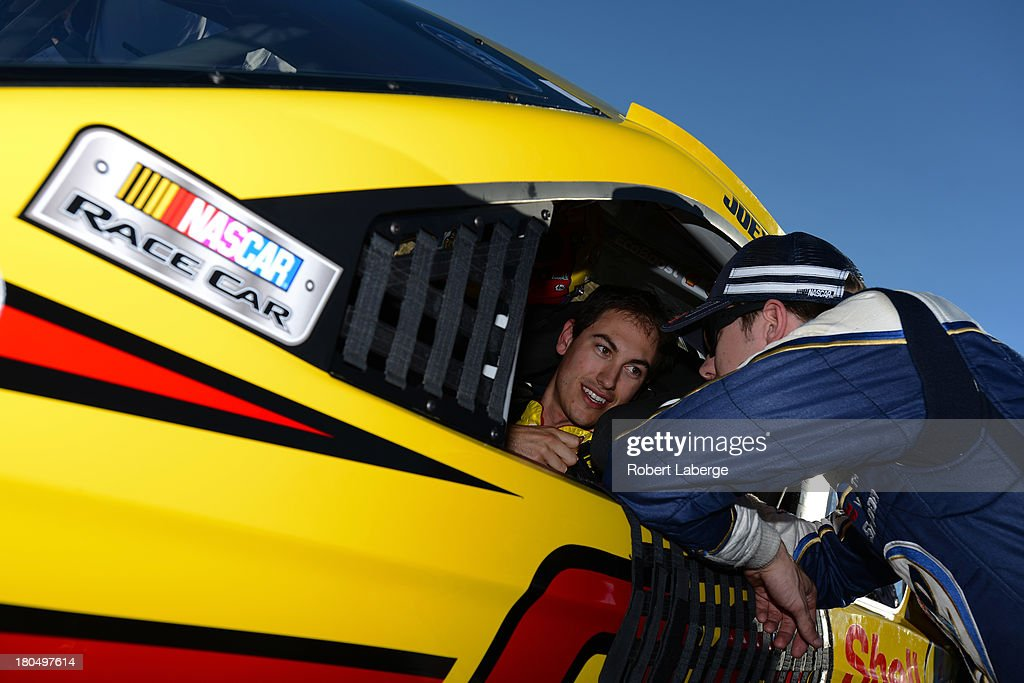 <a gi-track='captionPersonalityLinkClicked' href=/galleries/search?phrase=Joey+Logano&family=editorial&specificpeople=4510426 ng-click='$event.stopPropagation()'>Joey Logano</a>, driver of the #22 Shell-Pennzoil Ford, speaks with <a gi-track='captionPersonalityLinkClicked' href=/galleries/search?phrase=Brad+Keselowski&family=editorial&specificpeople=890258 ng-click='$event.stopPropagation()'>Brad Keselowski</a>, driver of the #2 Miller Lite Ford, during qualifying for the NASCAR Sprint Cup Series Geico 400 at Chicagoland Speedway on September 13, 2013 in Joliet, Illinois.