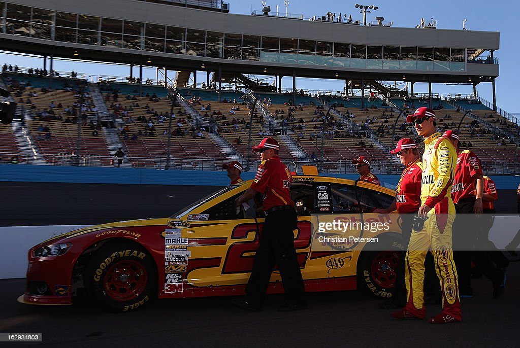 Joey Logano, driver of the #22 Shell-Pennzoil Ford, walks out with his car on the grid during qualifying for the NASCAR Sprint Cup Series Subway Fresh Fit 500 at Phoenix International Raceway on March 1, 2013 in Avondale, Arizona.