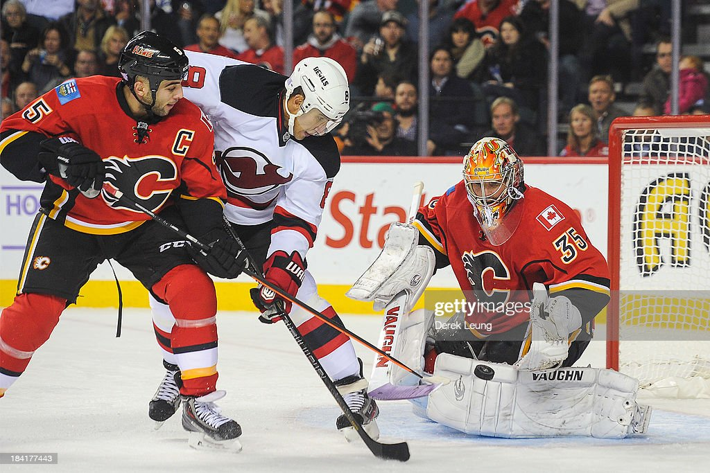 Joey MacDonald #35 of the Calgary Flames stops the shot of Dainius Zubrus #8 of the New Jersey Devils during an NHL game at Scotiabank Saddledome on October 11, 2013 in Calgary, Alberta, Canada.