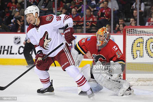 Joey MacDonald of the Calgary Flames tries to see past the screen of David Moss of the Phoenix Coyotes during an NHL game at Scotiabank Saddledome on...