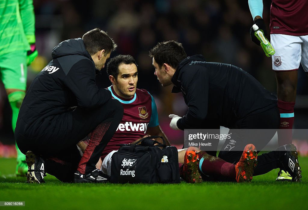 Joey O'Brien of West Ham United is given assistance during the Emirates FA Cup Fourth Round Replay match between West Ham United and Liverpool at Boleyn Ground on February 9, 2016 in London, England.