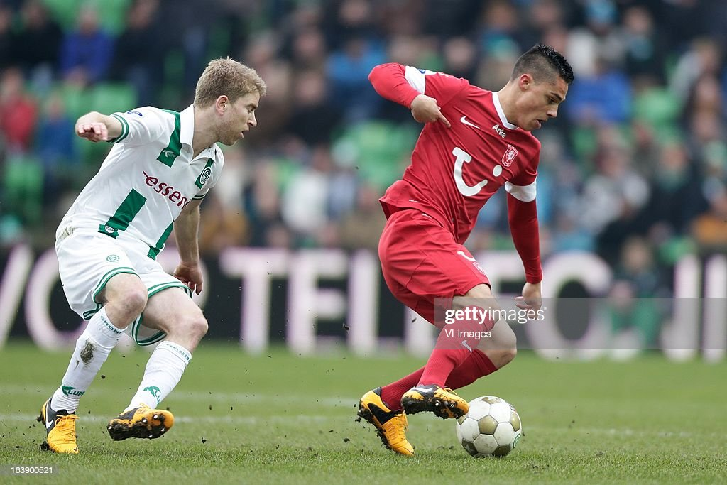 Joey Pelupessy of FC Twente (R) Michael de Leeuw of FC Groningen (L) during the Dutch Eredivisie match between FC Groningen and FC Twente at the Euroborg Stadium on march 17, 2013 in Groningen, The Netherlands