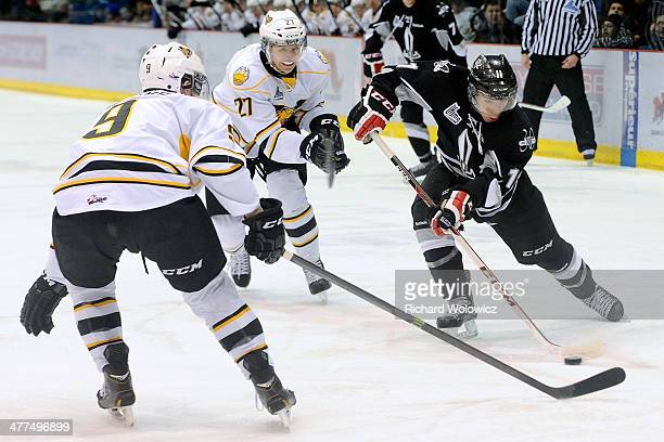 Joey Ratelle of the Drummondville Voltigeurs passes the puck in front of Yan Pavel Laplante and Gabriel Gagne of the Victoriaville Tigres during the...