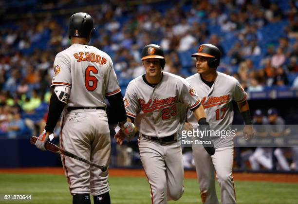Joey Rickard of the Baltimore Orioles and Ruben Tejada celebrate with Jonathan Schoop as they make their way to the dugout after scoring off of a...