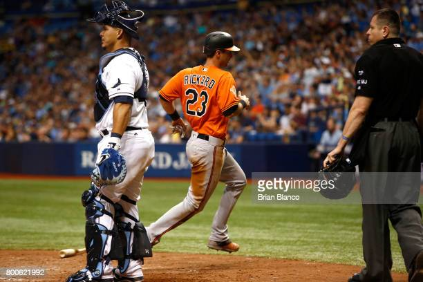 Joey Rickard of the Baltimore Orioles crosses home plate ahead of catcher Wilson Ramos of the Tampa Bay Rays to score off of a sacrifice fly by Manny...