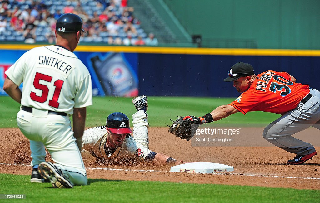 Joey Terdoslavich #25 of the Atlanta Braves dives in safely to third base against <a gi-track='captionPersonalityLinkClicked' href=/galleries/search?phrase=Placido+Polanco&family=editorial&specificpeople=213170 ng-click='$event.stopPropagation()'>Placido Polanco</a> #30 of the Miami Marlins at Turner Field on August 11, 2013 in Atlanta, Georgia.