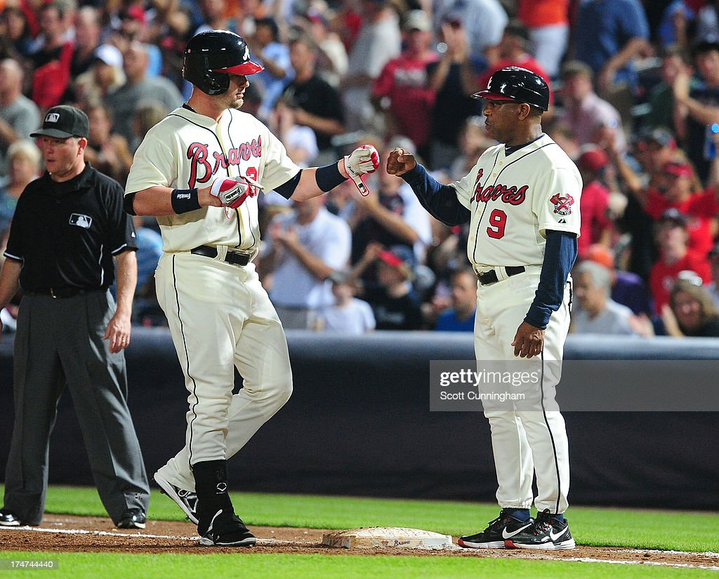 Joey Terdoslavich #25 of the Atlanta Braves is congratulated by Terry Pendleton #9 after hitting a run scoring single in the sixth inning against the St. Louis Cardinals at Turner Field on July 28, 2013 in Atlanta, Georgia.