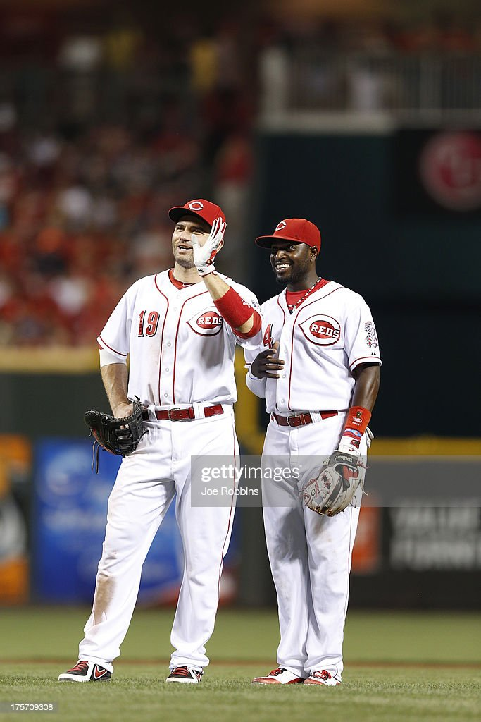 <a gi-track='captionPersonalityLinkClicked' href=/galleries/search?phrase=Joey+Votto&family=editorial&specificpeople=759319 ng-click='$event.stopPropagation()'>Joey Votto</a> #19 and Brandon Phillips #4 of the Cincinnati Reds wave to fans in the stands during a pitching change in the game against the Oakland Athletics at Great American Ball Park on August 6, 2013 in Cincinnati, Ohio. The Reds won 3-1.