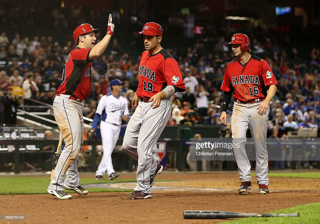 Joey Votto #19 and Cale Iorg #16 of Canada are congratulated by Chris Robinson #30 after scoring seventh inning runs against Italy during the World Baseball Classic First Round Group D game at Chase Field on March 8, 2013 in Phoenix, Arizona.