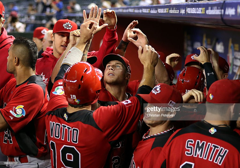 Joey Votto #19 of Canada high-fives Andrew Albers #27 and teammates in the dugout after scoring a seventh inning run against Italy during the World Baseball Classic First Round Group D game at Chase Field on March 8, 2013 in Phoenix, Arizona.