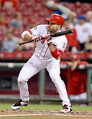 Joey Votto of the Cincinnati Reds attempts to bunt in the first inning during the game against the Chicago Cubs at Great American Ball Park on...