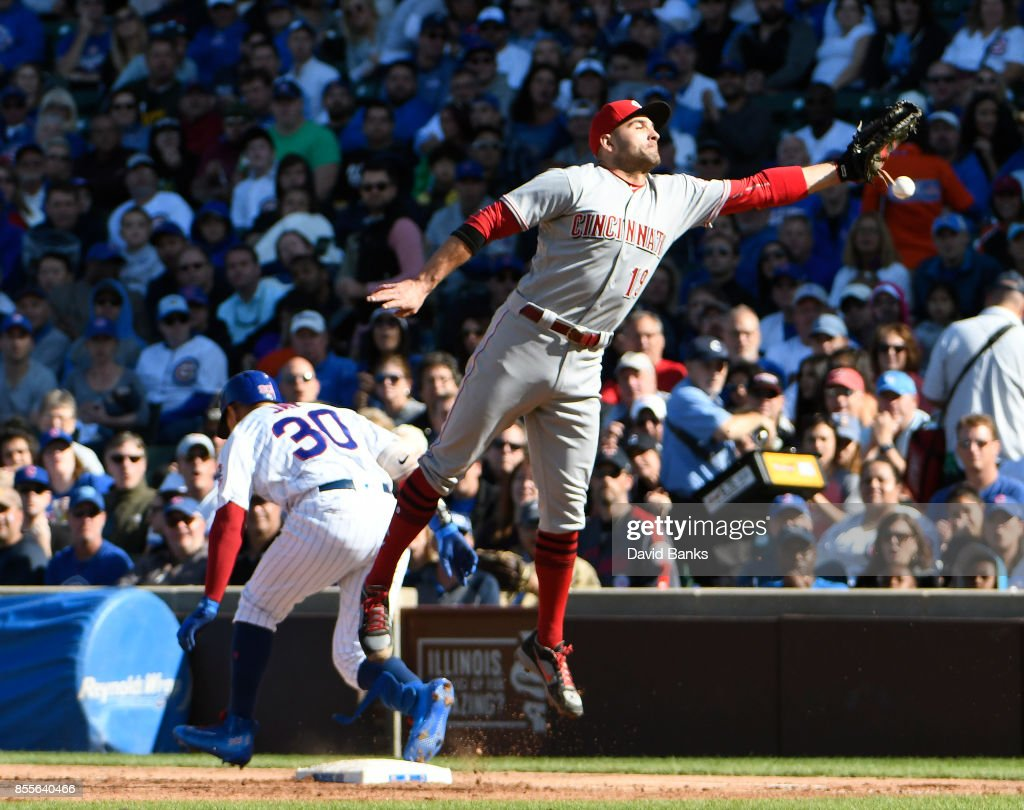 Joey Votto #19 of the Cincinnati Reds can't handle a throw as Jon Jay #30 of the Chicago Cubs is safe at first base on a bunt single during the fifth inning on September 29, 2017 at Wrigley Field in Chicago, Illinois.