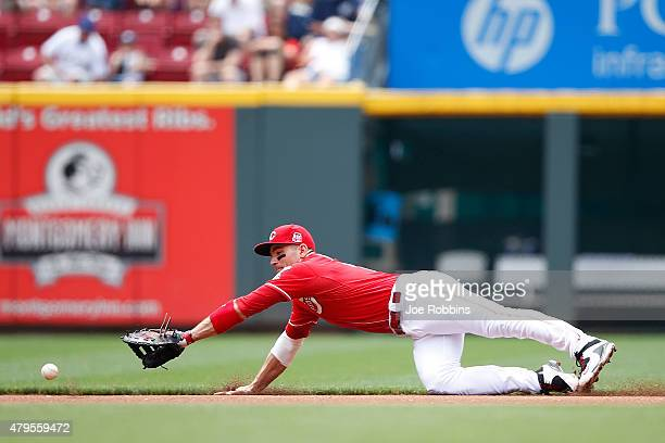Joey Votto of the Cincinnati Reds dives but is not able to field a ground ball in the first inning against the Milwaukee Brewers at Great American...