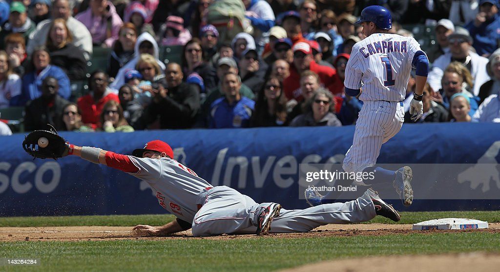 Joey Votto #19 of the Cincinnati Reds dives to make a catch on a late throw as Tony Campana #1 of the Chicago Cubs crosses first base at Wrigley Field on April 22, 2012 in Chicago, Illinois.