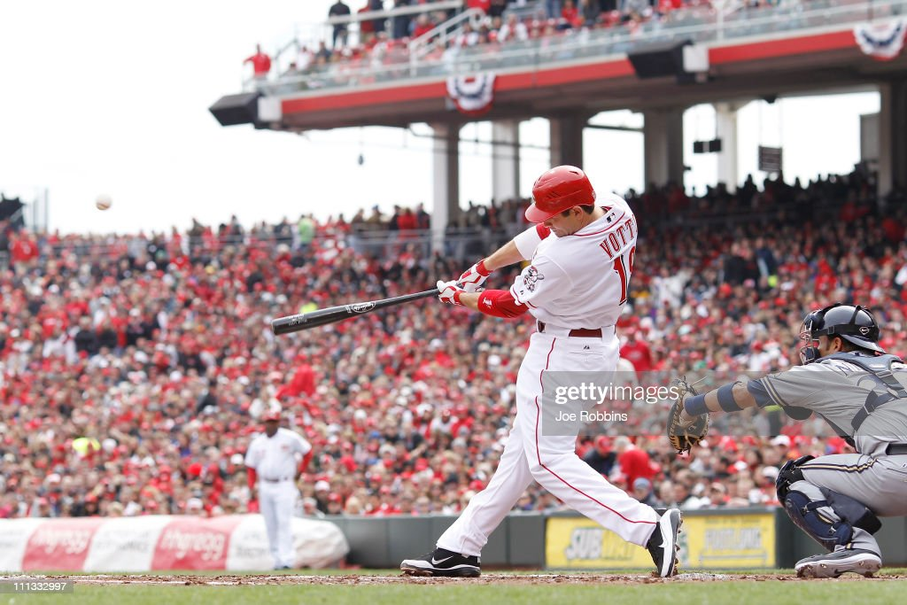 Joey Votto of the Cincinnati Reds hits a sacrifice fly in the first inning against the Milwaukee Brewers in the opening day game at Great American...