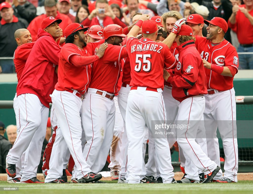 Joey Votto of the Cincinnati Reds is congratulated by teammates after a game winning hit in the bottom of the 9th inning during the game against the...