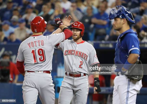 Joey Votto of the Cincinnati Reds is congratulated by Zack Cozart after hitting a tworun home run in the first inning during MLB game action as Luke...