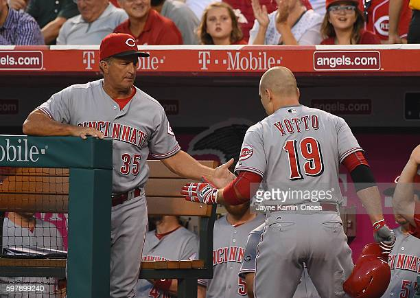 Joey Votto of the Cincinnati Reds is greeted at the dugout by coach Jim Riggleman after a solo home run in the first inning of the game at Angel...