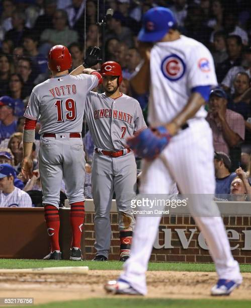 Joey Votto of the Cincinnati Reds is greeted by Eugenio Suarez after scoring a run in the 8th inning as Pedro Strop of the Chicago Cubs walks back to...