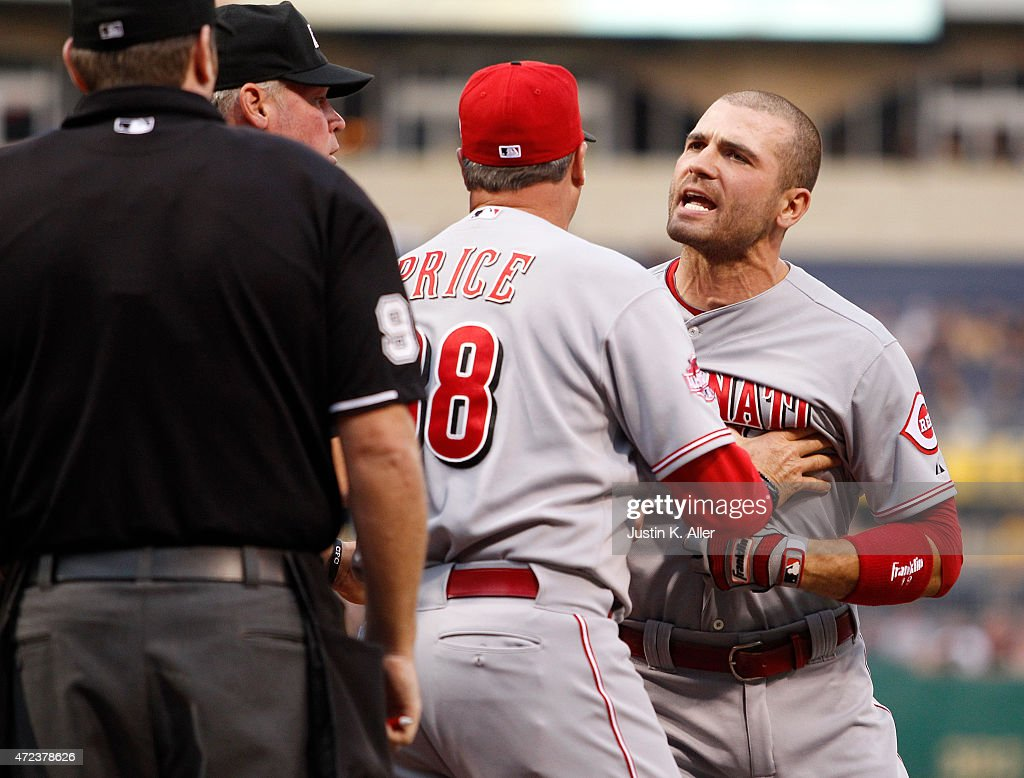 Joey Votto of the Cincinnati Reds is restrained by manager Bryan Price in front of home plate umpire Chris Conroy after being kicked out of the game...