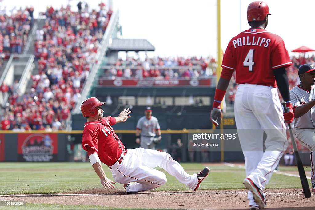 Joey Votto #19 of the Cincinnati Reds slides at home plate to score the tying run after a wild pitch in the ninth inning of the game against the Washington Nationals at Great American Ball Park on April 6, 2013 in Cincinnati, Ohio. The Nationals won 7-6 in 11 innings.