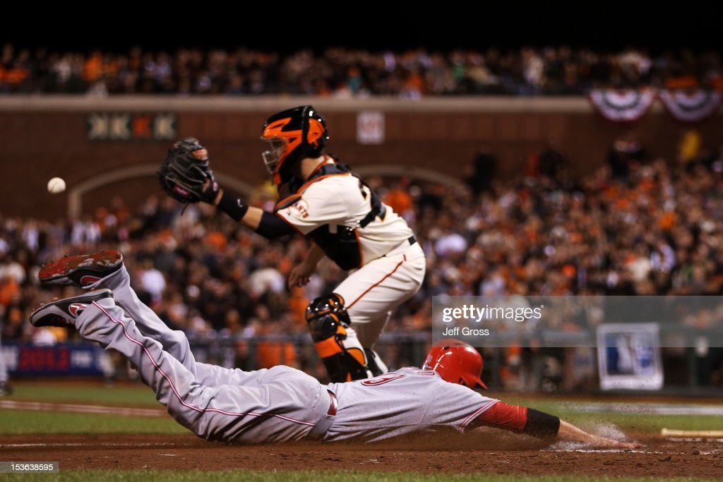 Joey Votto of the Cincinnati Reds slides into home base past catcher Buster Posey of the San Francisco Giants in the fourth inning of Game Two of the...
