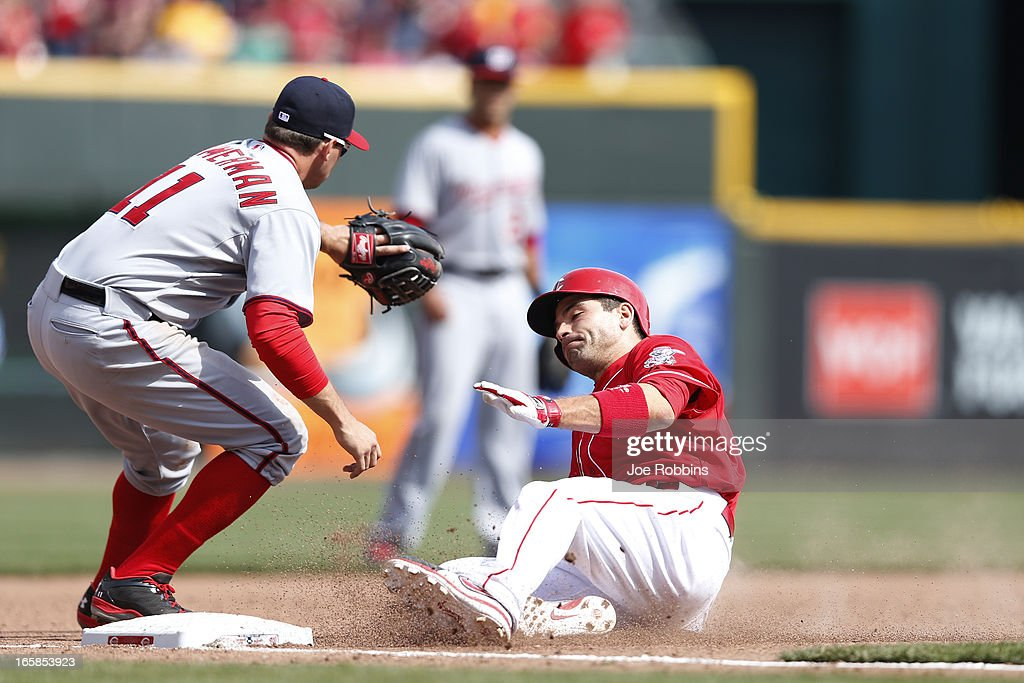 Joey Votto #19 of the Cincinnati Reds slides into third base with a triple in the ninth inning of the game against the Washington Nationals at Great American Ball Park on April 6, 2013 in Cincinnati, Ohio. The Nationals won 7-6 in 11 innings.