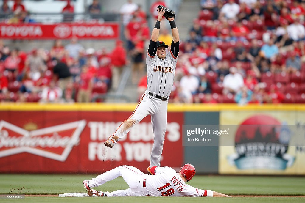 Joey Votto of the Cincinnati Reds steals second base ahead of the throw to Joe Panik of the San Francisco Giants in the first inning of the game at...