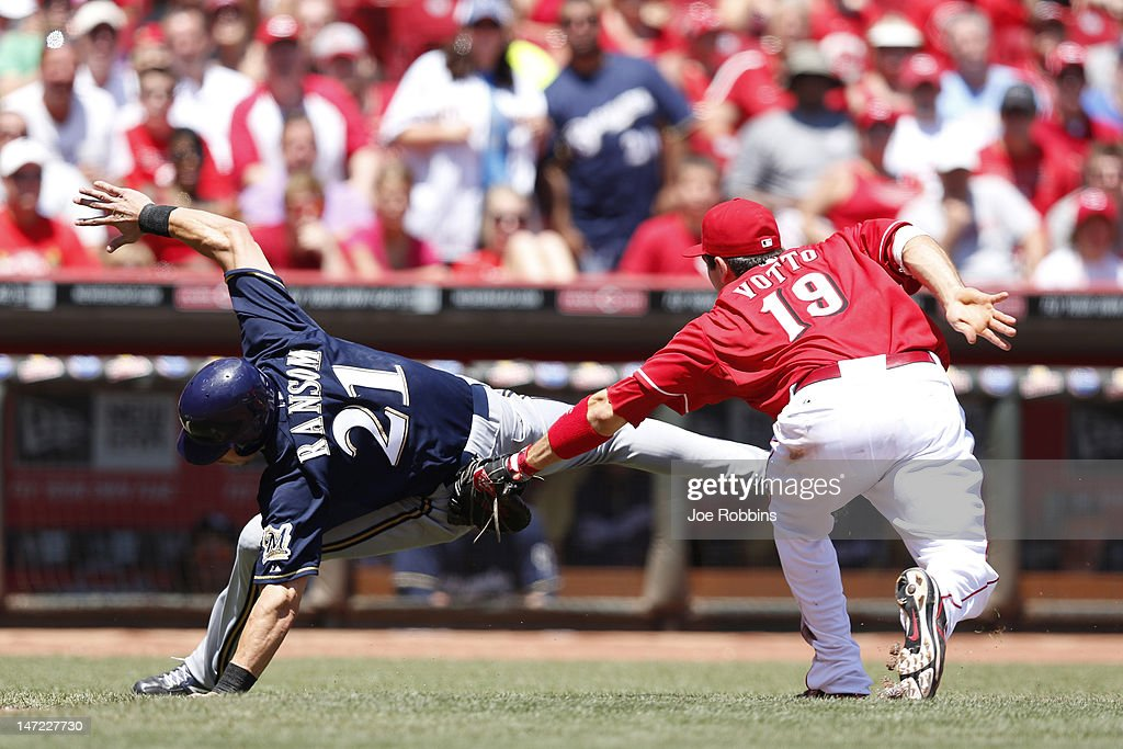 Joey Votto of the Cincinnati Reds tags out Cody Ransom of the Milwaukee Brewers on a rundown play between third and home plate during the game at...
